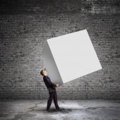 Businessman carrying white cube — Stock Photo