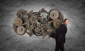 Businessman carrying cogwheel mechanism — Stock Photo