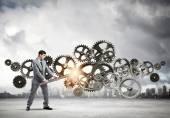 Businessman fixing gears mechanism — Stock Photo