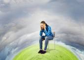 Woman sitting in chair on green planet — Stock Photo
