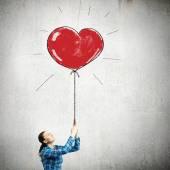 Woman holding heart shaped balloon — Стоковое фото
