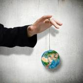 Hand holding Earth planet on rope — Stock Photo