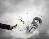 Hand crashing dollar sign — Stock Photo