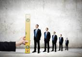 Hand measuring miniatures of businessman — Stock Photo