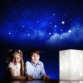 Boy and girl looking at model of house — Stock Photo