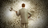 Businessman with wrench in hands and cogwheels — Stock Photo