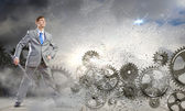 Businessman with wrench and cogwheels — Stock Photo
