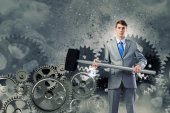 Businessman with hammer and cogwheels — Stock Photo