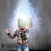 Woman hiding face behind book — Stock Photo