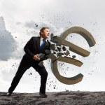 Businessman breaking stone euro sign — Stock Photo #54094087