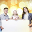 Happy family holding white blank banner — Stock Photo #54304477