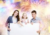 Happy family holding white blank banner — Stock Photo