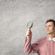 Guy looking in magnifying glass — Stock Photo #71054595