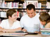 Father with sons in library — Stock Photo