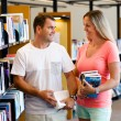 Couple in library with books — Stock Photo #74271365