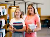 Girl and her mother in library — Stock Photo