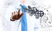 Businessman activating gears mechanism — Stock Photo