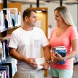 Couple in library with books — Stock Photo #77431290