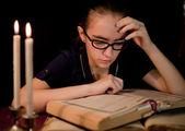 Girl reading book in dark library — Stock Photo