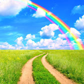 Rural landscape with old road and rainbow — Stock Photo