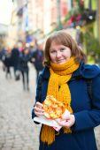 Cheerful girl with pretzel on Christmas market — Stock Photo