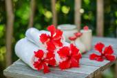 Spa setting with towels and red hibiscus flowers — Stock Photo