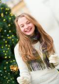 Girl with a sparkler near brightly Christmas tree — Stock Photo