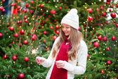 Ragazza con un sparkler vicino brillantemente albero di natale — Foto Stock