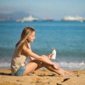 Young woman applying sunscreen on her legs — Stock Photo