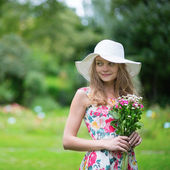 Young girl in white hat holding flowers — Stockfoto