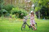 Beautiful girl with bicycle in the countryside — Stock fotografie