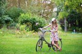 Beautiful girl with bicycle in the countryside — Stockfoto