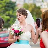 Damigella d'onore è prendendo la foto di una giovane sposa felice — Foto Stock