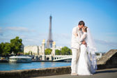Bride and groom on the Seine embankment in Paris — Stock Photo