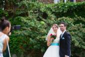 Bride and groom posing to photogtrapher — Стоковое фото