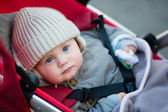 Little boy with blue eyes in a stroller — Stock Photo