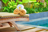 Towels with white frangipani flowers near the pool — Foto de Stock