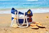 Beach bag, flip flops and sunscreen on beach  — Stockfoto