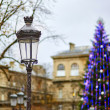 Streetlamp and Christmas tree in the background — Stock Photo #60178229
