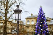 Streetlamp and Christmas tree in the background — Stock Photo