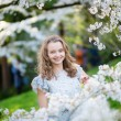 Beautiful young girl in cherry blossom garden — Stock Photo #60699175