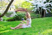 Girl eating sushi in cherry blossom garden — Stock Photo