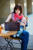 Young mother with her baby boy working in cafe — Stock Photo