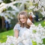 Beautiful girl in cherry blossom garden — Stock Photo #61472849