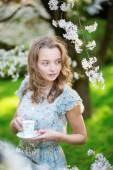 Girl drinking tea in cherry garden on a spring day — Stock Photo