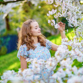 Young woman in cherry blossom garden — Stock Photo
