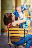 Young mother with her little son in a street cafe — ストック写真