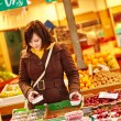 Young woman buying fresh fruits at market — Stock Photo #64267291