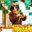 Young woman buying fresh fruits at market — Stock Photo #64267333
