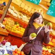 Young woman buying fresh fruits at market — Stock Photo #64267407